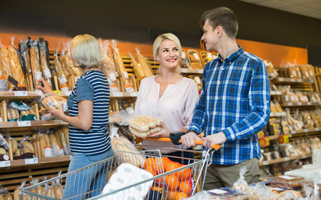 provision: Happy smiling family looking at assortment of bread rolls and bagels Stock Photo