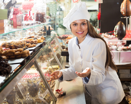 Brunette smiling woman selling fine chocolates and confectionery in cafe