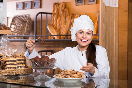 shopgirl: Happy young shopgirl working in bakery with bread and different pastry