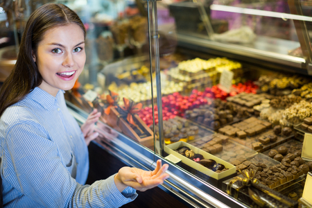 shopgirl: Smiling brunette girl buying dark and white chocolate with fillings Stock Photo