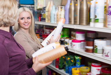 vend: Happy adult women chooses shampoo in cosmetic store