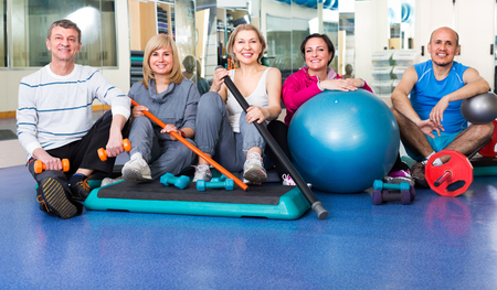 lifestile: Group of  positive mature men and women after exercising in  gym with sport equipment