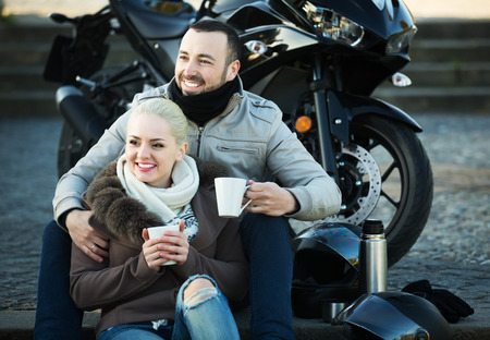 sandwitch: Young couple posing near motor bike with sandwitches and coffee and smiling Stock Photo