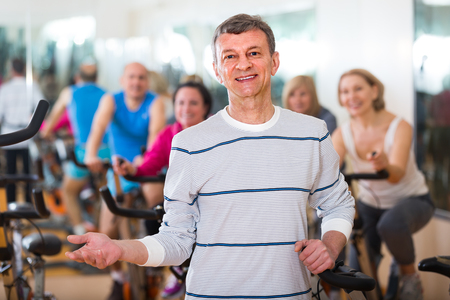 lifestile: Man on fitness  bicycle training with group of people