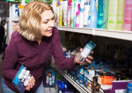 homeware: Aged woman chooses bulbs in hardware shop Stock Photo