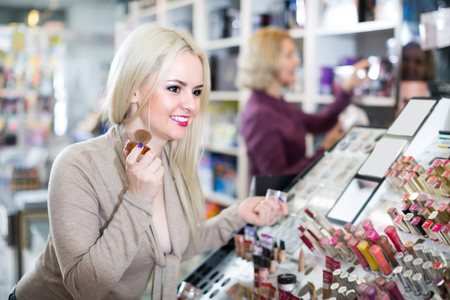 beauty store: Portrait of happy girl selecting face powder in beauty store Stock Photo