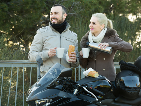 sandwitch: happy american couple posing near motor bike with sandwitches and coffee Stock Photo