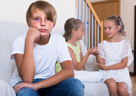 banter: Two little girls talking and sulky boy sitting separately at home. Focus on boy