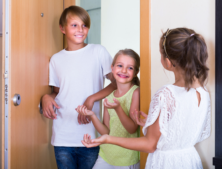 russian girls: Two happy russian girls with teenage boy meeting in doorway and laughing