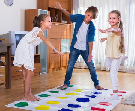 twister: Two cheerful little girls and teenage boy playing twister at home