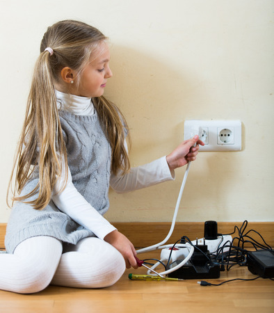 children clothing: Small girl wearing ponytails playing with electricity and smiling