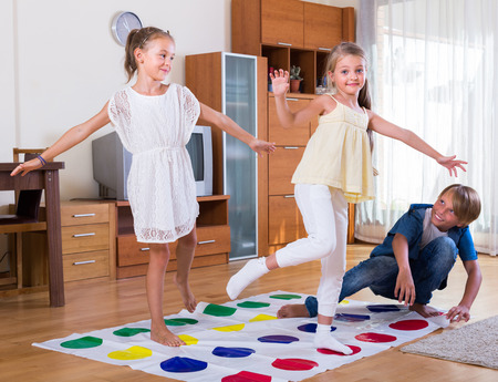 twister: Two cheerful little girls and teenage boy with twister at home Stock Photo