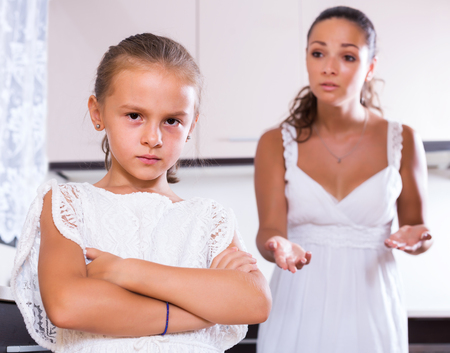 berate: Sad girl and angry mother arguing in the kitchen