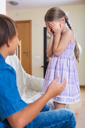 berate: Unhappy little children having serious fight in domestic interior Stock Photo