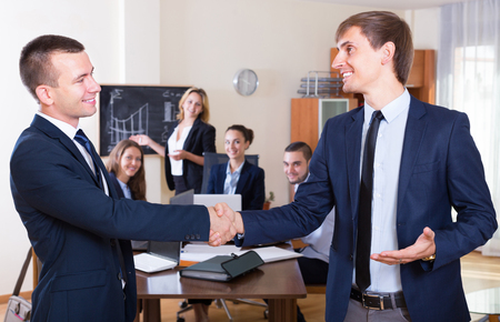 deal in: Successful managers shaking hands after closing deal in office Stock Photo
