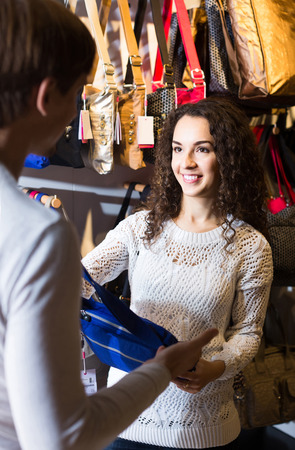 shopgirl: Positive american customers looking at stylish female handbags in store