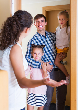 expected: Hospitable householder meeting expected happy guests at doorway Stock Photo