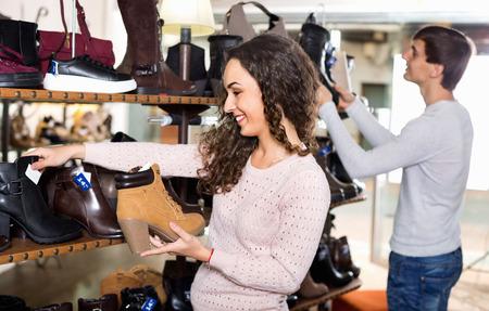 comprando zapatos: Sonriendo zapatos de invierno Joven pareja comprar en una tienda de zapatos Foto de archivo