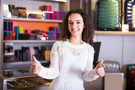 shopgirl: Portrait of smiling young brunette selling wallets and bags in store