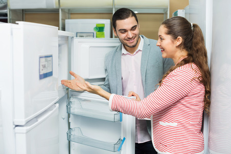 domestic appliances: Satisfied couple looking at large fridges in domestic appliances section