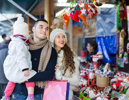 ornamentations: A young handsome man with his wife and daughter buying christmas ornamentations at a christmas market. Shallow focus. Focused on man.