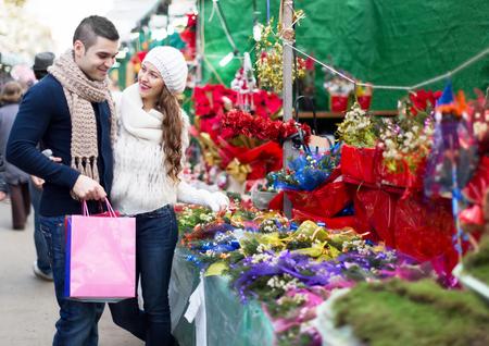 festal: A couple at a christmas fair buying Poinsettia. Shallow focus