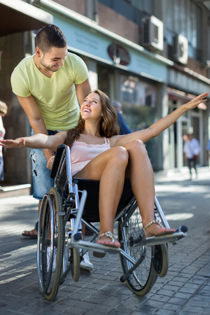 invalidity: Happy young girl in wheelchair playing with her friend outdoor. Focus on man Stock Photo