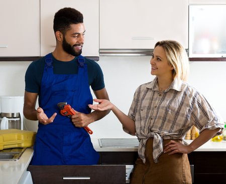 thanking: Happy woman thanking black professional plumber for work