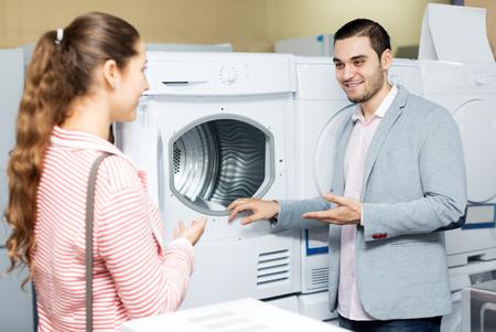 lavadora con ropa: Sonriente pareja de familia comprar nueva lavadora de ropa en un supermercado. Centrarse en el hombre Foto de archivo
