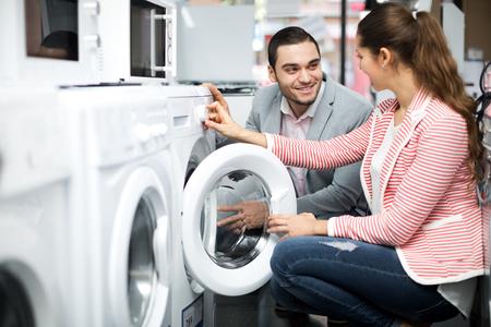 lavadora con ropa: pares de la familia joven y bella la compra de nueva lavadora de ropa en un supermercado. Centrarse en el hombre
