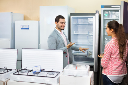 purchases: Smiling beautiful couple looking at large fridges in domestic appliances section