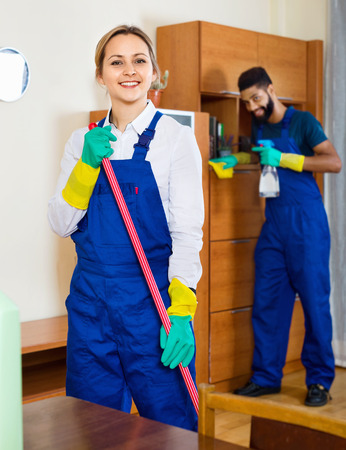 dusting: Smiling young cleaners cleaning and dusting in ordinary house