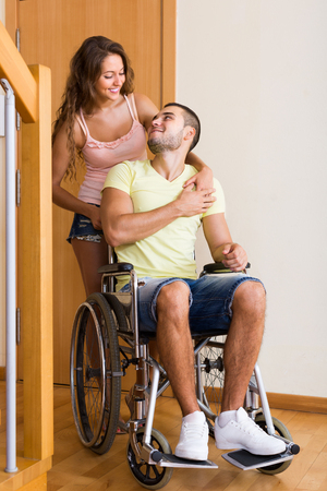 coming home: Young positive woman and her disabled husband in wheelchair coming home Stock Photo