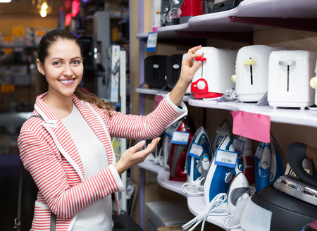 appliances: Smiling female customer looking at toasters in domestic appliances section Stock Photo