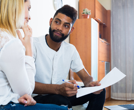 interracial family: Interracial family couple filling papers for mortgage indoors Stock Photo