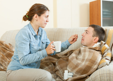 diseased: Adult girl giving giving drugs to diseased man at home Stock Photo