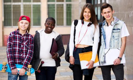 Happy group of teenager posing outside school with papers for study