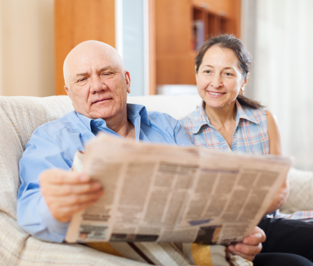 gladful: mature couple reading newspaper  together in home
