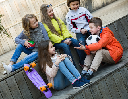 blabbing: Group of cheerful junior school children chatting and laughing outdoors