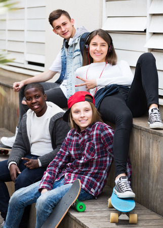blabbing: Happy ordinary teens spending time together in sunny day Stock Photo