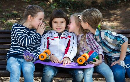 blabbing: Little kids whispering in other ears in city street
