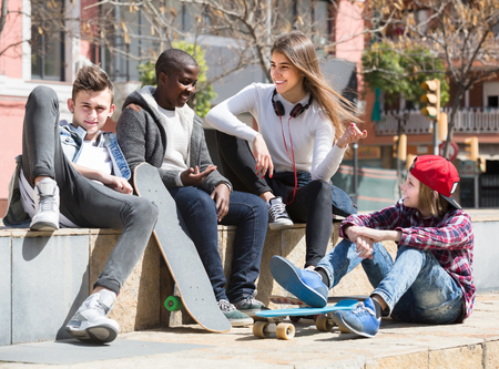 blabbing: girl and three positive european boys hanging out outdoors and discussing something Stock Photo