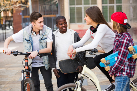 blabbing: Group of teens chatting near bikes  in the town Stock Photo