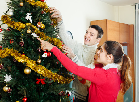 decorating christmas tree: Happy parents and baby girl decorating Christmas tree Stock Photo