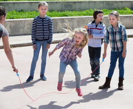 Happy girl jumping while jump rope game with friends outdoor Stock Photo