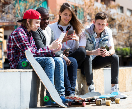teens playing: Friendly teens playing on smarthphones and listening to music