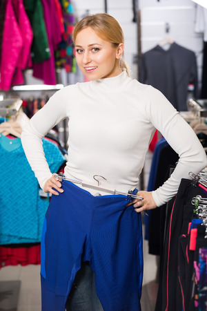 fitting in: Smiling blonde girl choosing and fitting new fitness pants in the sport store Stock Photo