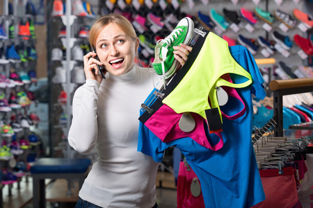 Young smiling girl picking a sport bra in the shop while talking to the phone