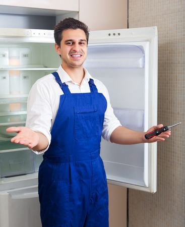 refrigerator kitchen: Smiling young handyman repairing refrigerator in kitchen Stock Photo