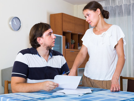 thoroughly: Worried couple counting family budget with documents at the desk at home